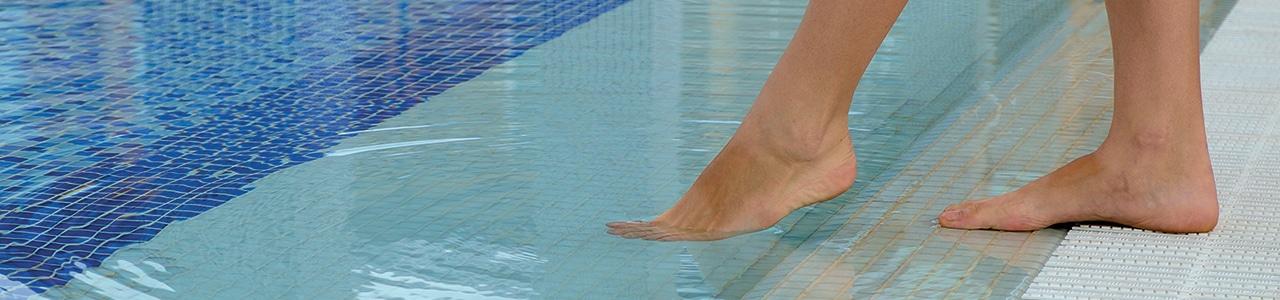 foot dipped in swimming pool